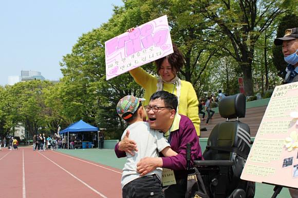 Puliphana hugging a child under a FREE HUG sign held by a woman