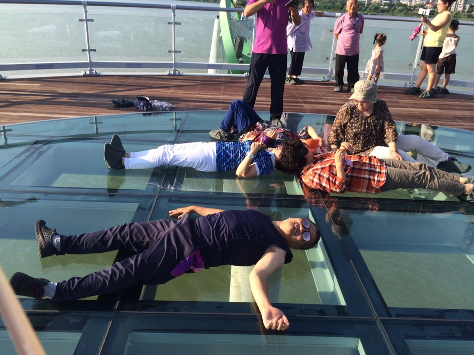 Puliphana lying face up on the glass floor of a deck over the water