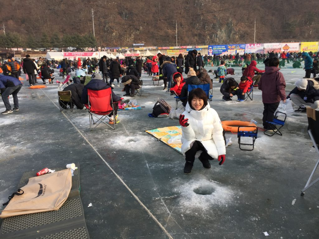 Heejeong with other people fishing, alongside a hole in the ice