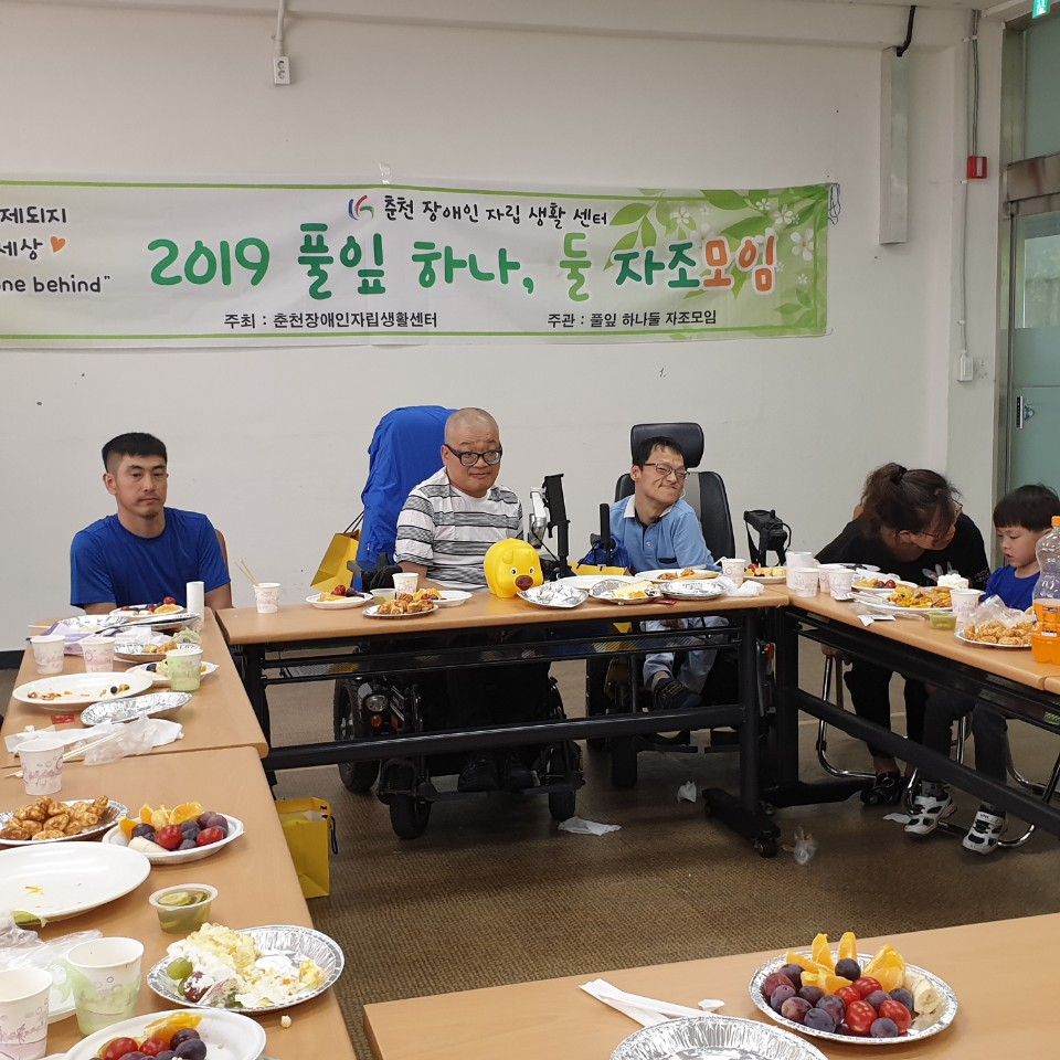 Puliphana and others sitting at a table of food in front of a banner with Korean text