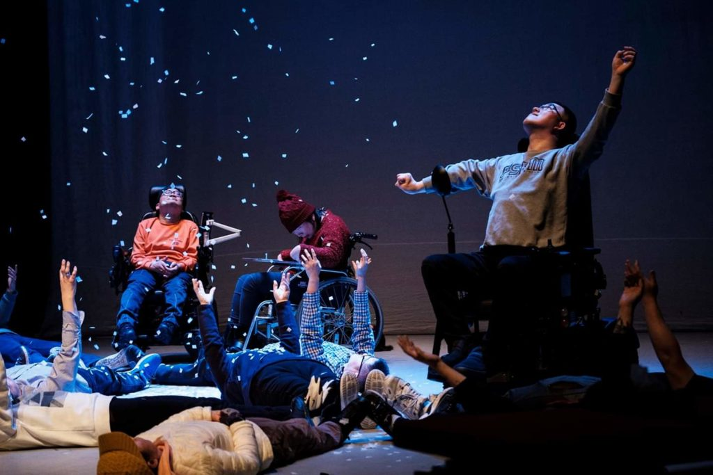 Performers in wheelchairs and laying on the floor, arms stretched towards the sky, as paper snowflakes fall from above