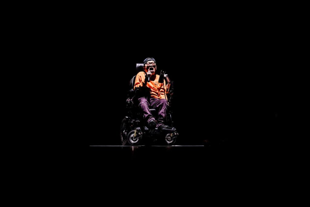 Puliphana in his wheelchair speaking into a microphone surrounded by blackness