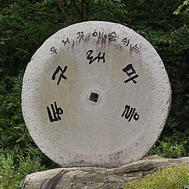 Large circle-shaped stone sign with Korean text engraved