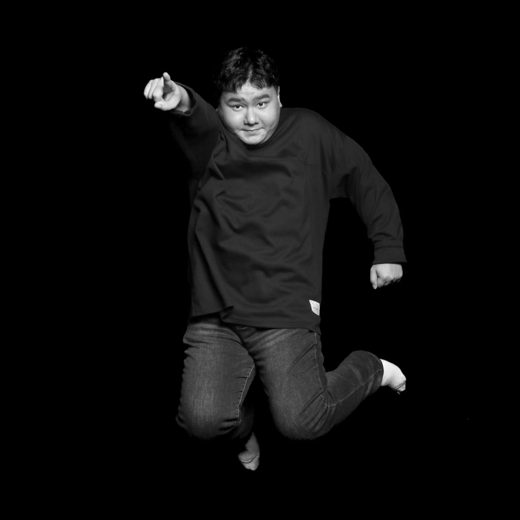 Black and white portrait of Yongin jumping and pointing towards the camera