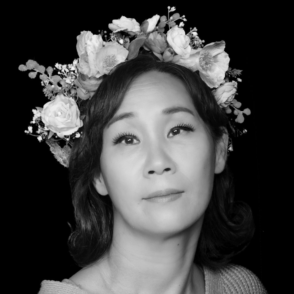 Black and white portrait of Sujin wearing a floral crown
