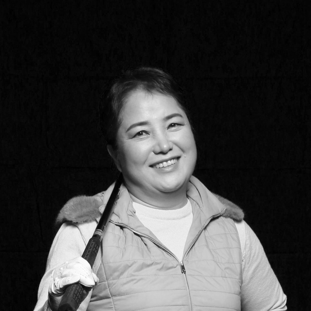 Black and white portrait of Yeonsu smiling with a golf club over her shoulder