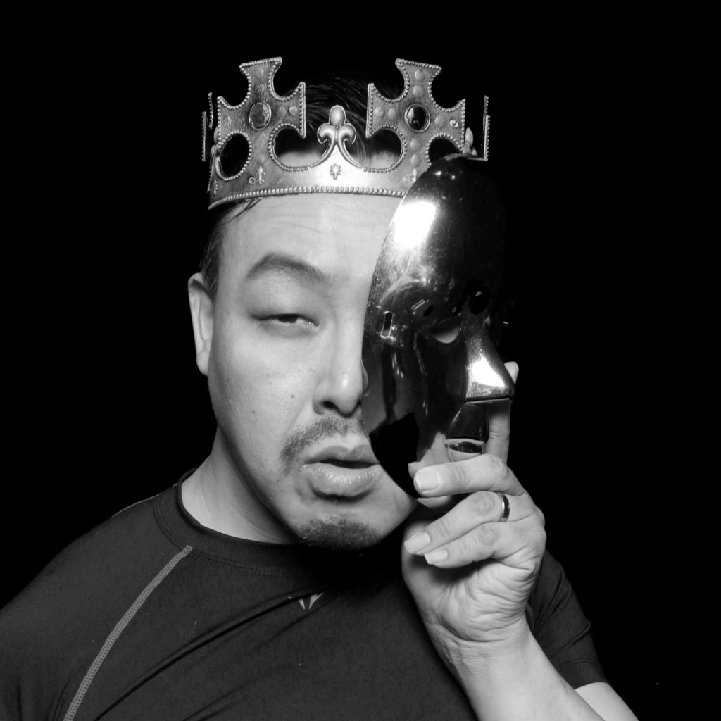 Black and white portrait of Jongmin wearing a crown and holding a theatre mask to his face