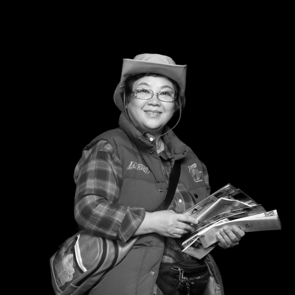 Black and white portrait of Jeongsun wearing a hat holding travel maps
