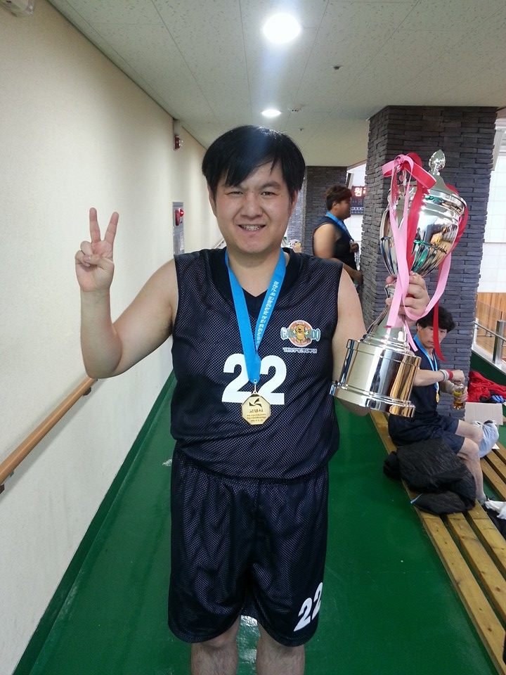 Smiling Hobin in basketball jersey, wearing a medal, and holding a large trophy