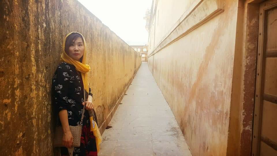Sujin in a yellow scarf standing in a long narrow alleyway