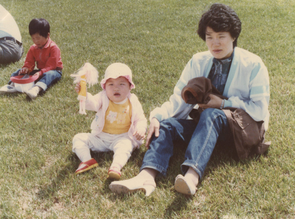 Yoonseon as a baby with her mum, sitting on the grass