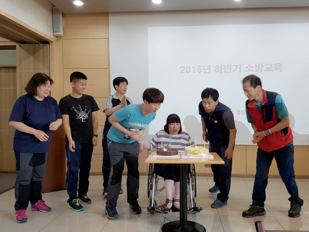 YoonSeon seated behind two cakes, blowing out the candles with others.
