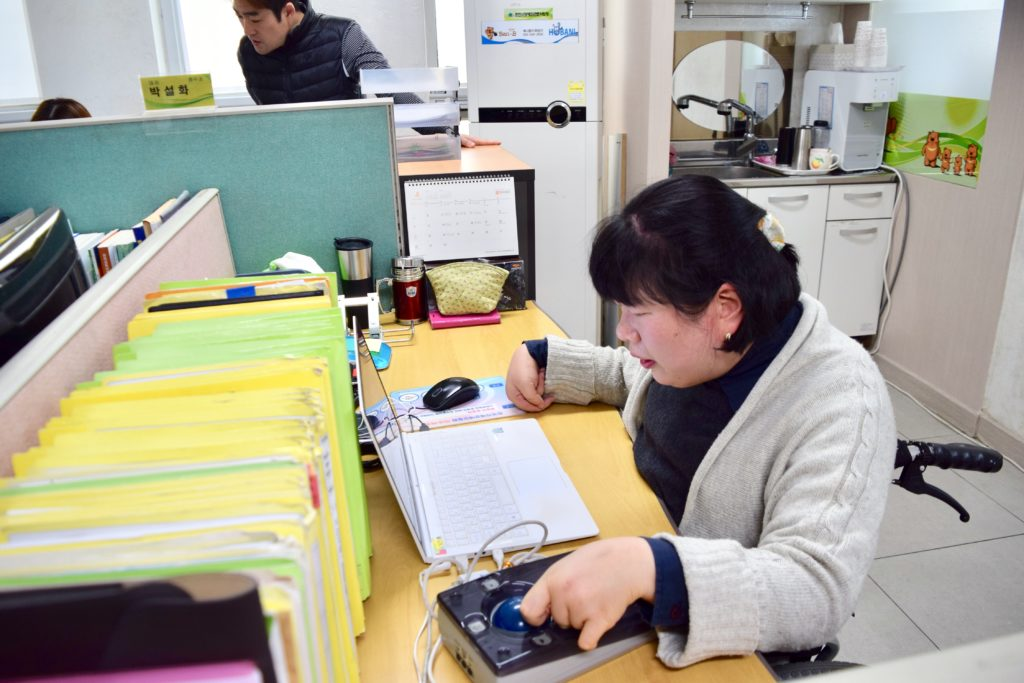 Yoonseon working at a laptop computer in an office