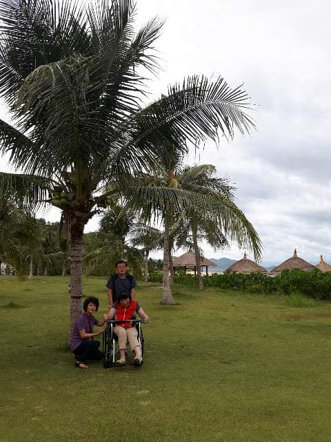 Yoonseon under a palm tree with two others, with grass huts in the background