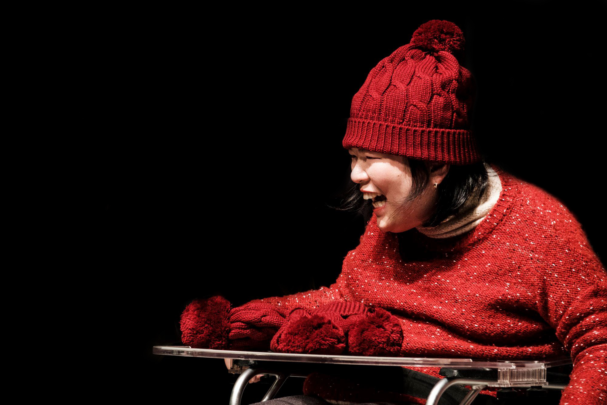 Yooseon smiling on stage, wearing a red sweater and beanie