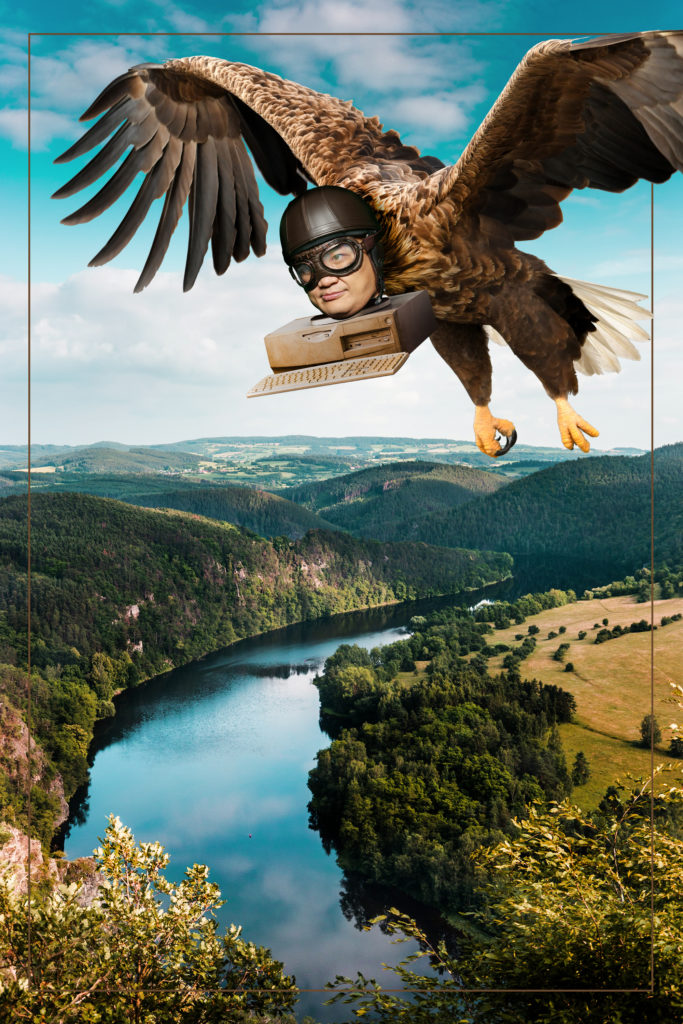 Puliphana's face attached to computer parts and the body of an eagle, flying high above a river in the countryside