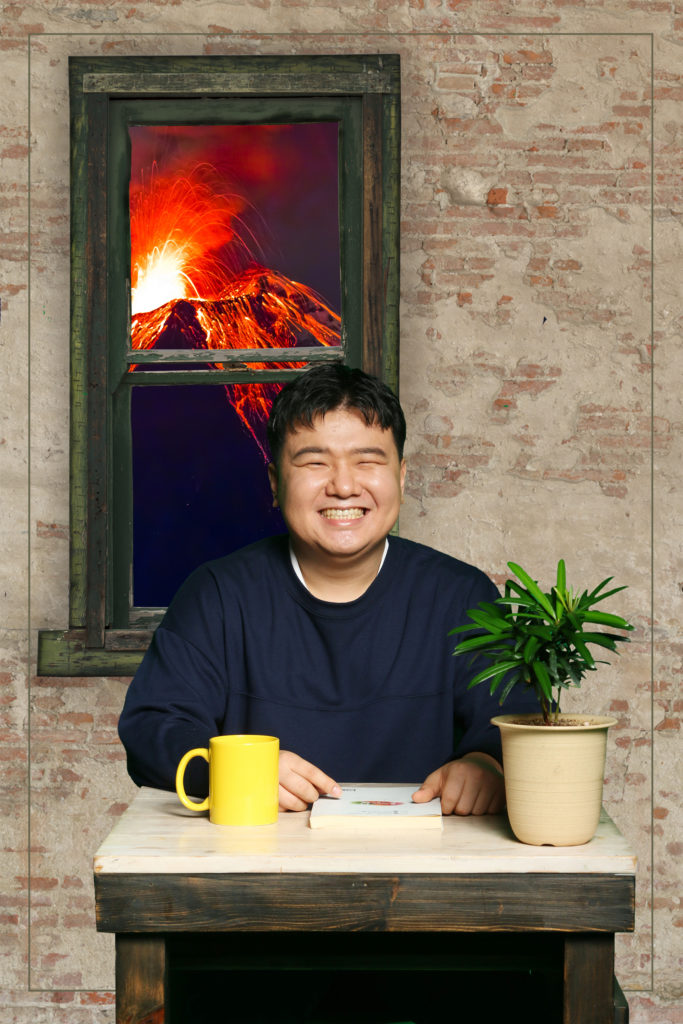 Yongin sitting and smiling at a table. Through the window behind him, a volcano is erupting outside.